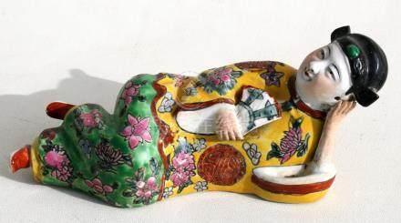 A Chinese famille rose figure depicting a recumbent lady holding a fan, 18cms (7ins) long.