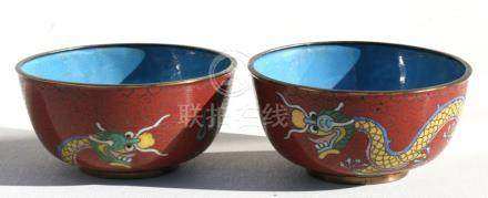 A pair of Chinese cloisonne bowls decorated with dragons on a red ground, 11cms (4.25ins) diameter.