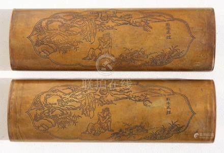 A pair of Chinese patinated bronze wrist rests decorated with a figure in a landscape with four-