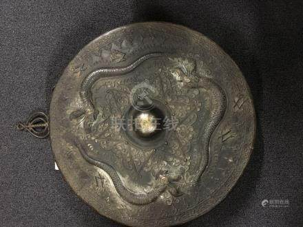 A large bronze Chinese gong decorated with cloud dragons.