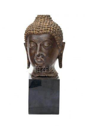 A bronze Buddha head. With elongated ears and hair in tight curls. With remnants of gilding. China,