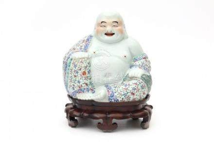A Chinese famille rose budai holding prayer beads in one hand and a bag in the other. On wooden