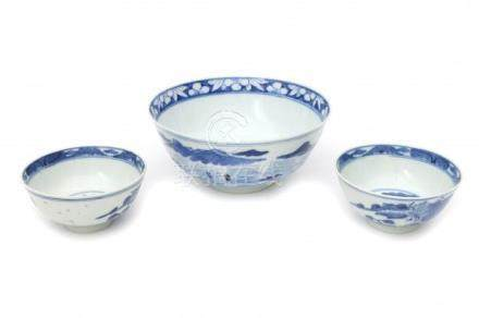 A Chinese blue and white bowl decorated with a landscape and two bowls decorated with pagodas. All