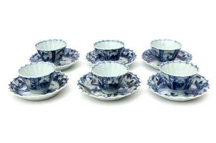 A set of six Chinese blue and white cups and saucers, each decorated with a fisherman in a river-