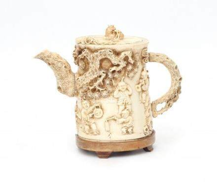 A Chinese richly carved ivory teapot, decorated with playing children, the spout and handle in the