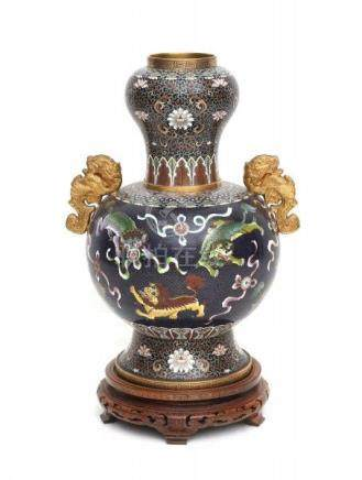 A large Chinese cloissoné vase with two gilt handles, decorated with foo dogs. On wooden stand.