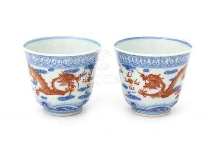 Two Chinese blue and white cups decorated in red with two dragons and the flaming pearl. Marked