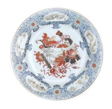 A Chinese export Imari style plate, decorated with a scroll painting surrounded by flowers.