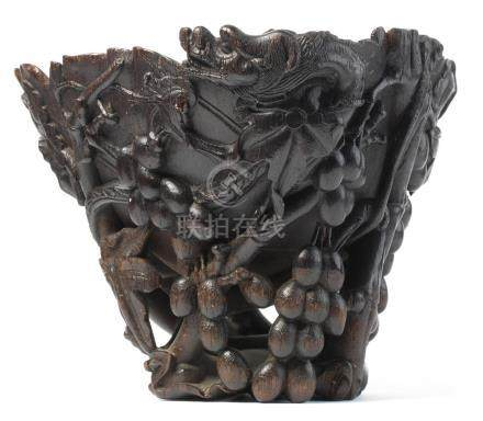 An exceptionally rare and very large rhinoceros horn 'three-dragons and grapevine' wine receptacle 17th/18th century