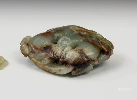 A Chinese jade carving of two bixies, in dark celadon jade with reddish-brown inclusions, the bixies