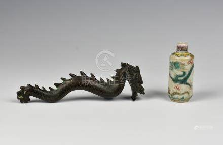 A Chinese bronze dragon, probably originally a handle, with silver metal inlaid scale decoration,