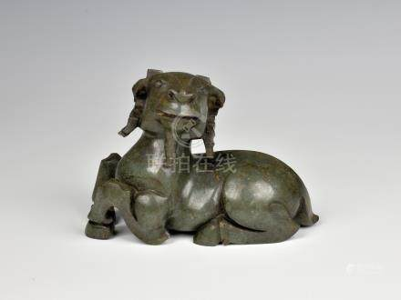A Chinese 20th century archaic jade figure of a recumbent ram, dark green, 6½in. (16.5cm.) long.