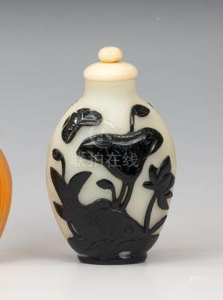 A Chinese black overlay white glass snuff bottle, 19th century, the elongated ovoid body decorated