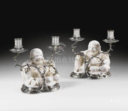 A rare pair of French silver-mounted two-light candelabra formed as white porcelain magot figures, the mounts Paris, 1726-1732