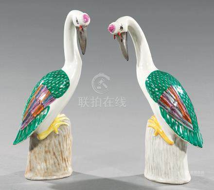 Pair of Chinese Polychrome Porcelain Cranes, 20th c., modeled in mirror image, perched atop a rock