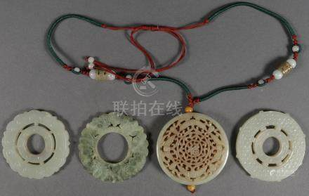 FOUR CHINESE CARVED JADE DISC FORM PENDANTS QING