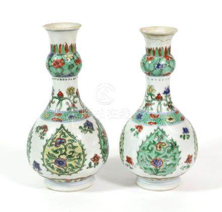A Pair of Chinese Porcelain Bottle Vases, Kangxi, with garlic necks, painted in famille verte
