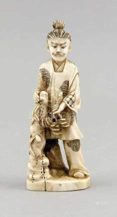 Okimono, Japan, 19. Jh., Mann an schmalen Fels gelehnt, einen Pinienzweig in der Handhaltend.