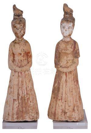 A PAIR OF CHINESE POTTERY FIGURES OF FEMALE ATTENDANTS, TANG DYNASTY (618-907) each standing in long