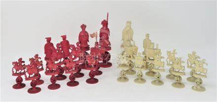 A CHINESE CARVED IVORY CHESS SET, PROBABLY CANTON, CIRCA 1900 natural or red stained, carved as a