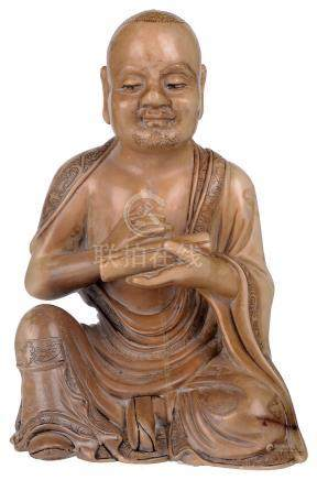 A CHINESE SOAPSTONE FIGURE OF A LUOHAN, 19TH CENTURY the beige soapstone figure carved seated