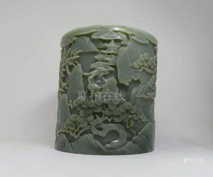 A CHINESE CELADON JADE 'IMMORTALS' BRUSHPOT the cylindrical body deeply carved around the exterior
