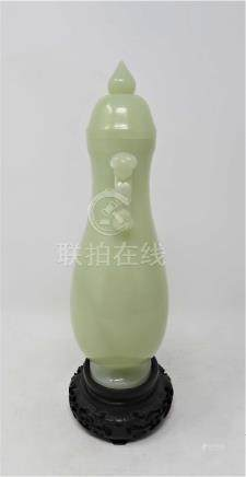 A CHINESE CELADON JADE PEAR-SHAPED VASE AND COVER the flattened pear-shaped body rising from a short