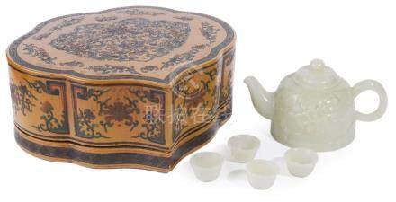 A CHINESE PALE CELADON JADE TEAPOT AND COVER AND FOUR CUPS the beehive-shaped body set to one side