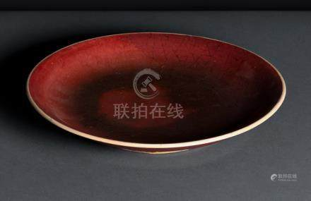 A LANGYAO-GLAZED PLATE, China, 18th/19th ct. Heavily potted with an uneven crazed red glaze, thinnin