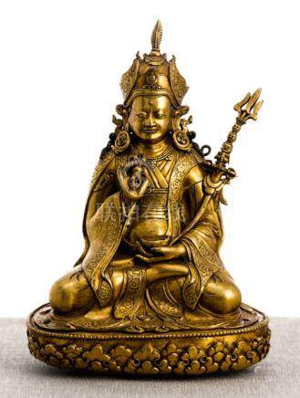 A GILT-BRONZE FIGURE OF PADMASAMBHAVA, Bhutan, 18th/19th ct., seated in vajrasana on a lotus base wi