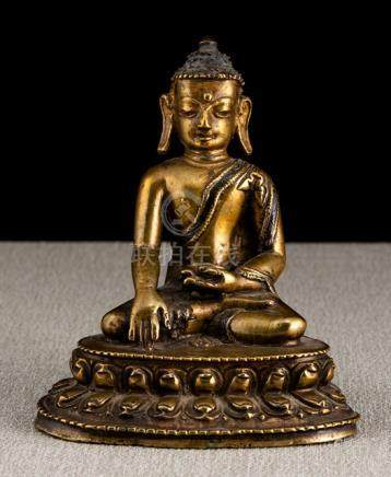 A COPPER-INLAID BRONZE FIGURE OF BUDDHA SHAKYAMUNI, TIBET, 15th ct., seated in vajrasana on a lotus