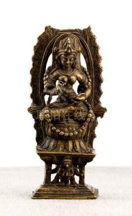 A BRONZE FIGURE OF THE FEMALE DEITY NA GA RAJA, KASHMIR REGION, ca. 11th ct., seated in vajrasana on
