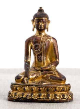 A GILT-BRONZE FIGURE OF BUDDHA SHAKYAMUNI, TIBET, late 15th ct., seated in vajrasana on a lotus base
