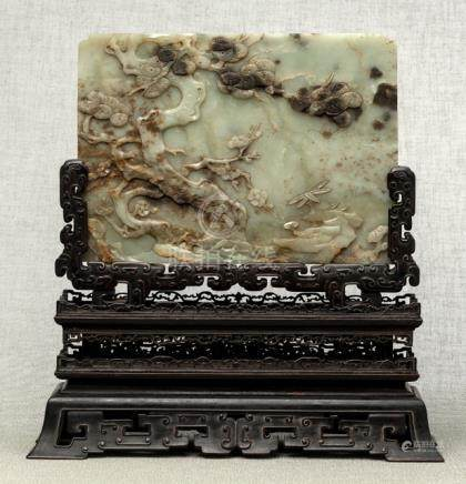 AN ENGRAVED AND CARVED JADE PANEL MOUNTED AS HARDWOOD TABLE SCREEN, China, probably Qianlong period.