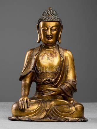 AN IMPORTANT GILT-BRONZE FIGURE OF BUDDHA SHAKYAMUNI, CHINA, Ming dynasty, 16th ct., wood base. Seat