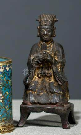 A BRONZE FIGURE OF A DIGNITARY, CHINA, late Ming dynasty, seated in European fashion on a throne wit