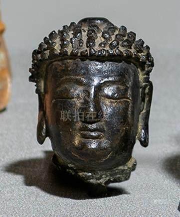 A BRONZE HEAD OF BUDDHA SHAKYAMUNI, CHINA, Ming dynasty, ca. 16th ct., his head cast with a serene f