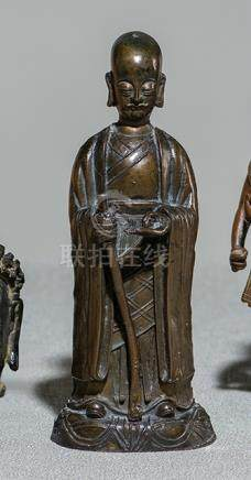 A BRONZE FIGURE OF A MONK, CHINA, late Ming dynasty, standing on a shaped base with his right hand h