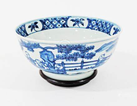 A Chinese blue and white bowl bearing Ming Dynasty, Xuande markings on wooden base, W20cm. (2)