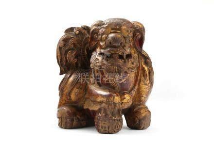 China-LöweChina, 19./20. Jh., Holz geschnitzt, H: 18 cm. Unter der Vorderpfote eine strukturierte