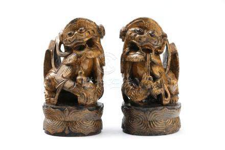 Ein paar Fo - HundeChina, 20. Jh., Holz geschnitzt, H: 25 cm. Ein paar Fo-Hunde auf Sockel