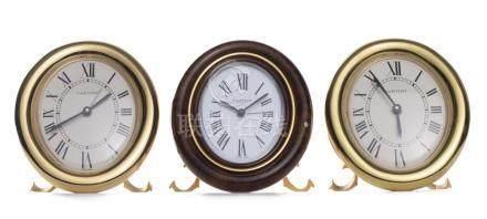 Cartier, Must de, 3 pendulettes réveil. Boîtier de forme ovale en métal doré reposant sur des pieds en forme de C