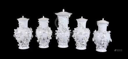 A Garniture of five hard-paste porcelain flower-encrusted baluster vases and associated plaster cove