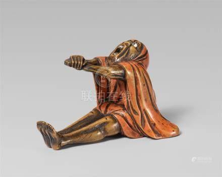 A wood and lacquer okimono-type netsuke of Daruma after meditation. Late 19th century