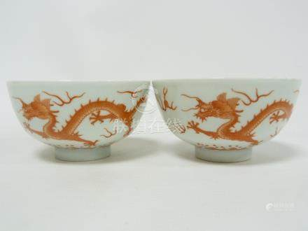 Pair of Chinese porcelain tea bowls decorated with dragons in overglaze iron red.