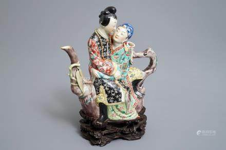 A Chinese famille rose semi-erotic teapot on wooden stand, Republic, 20th C.