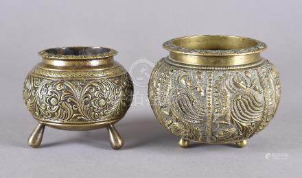 Two Indian spherical brass bowls, each with engraved decoration on three feet, 12 cm and 10.5 cm
