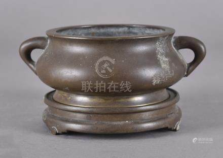 An 18th Century Chinese bronze censer on stand, the bowl of squat globular form with twin lug