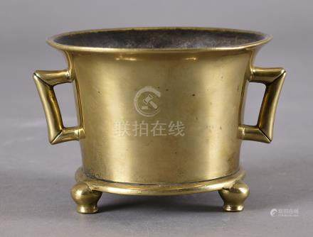 An 18th Century Chinese bronze twin handled censer, the circular straight body with flared rim and