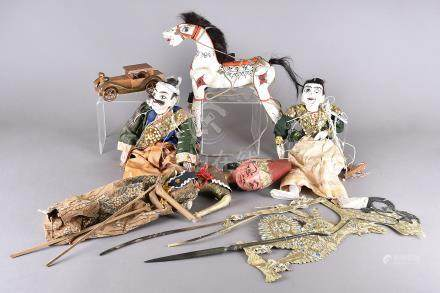 A collection of Indonesian and central Asian puppets, mostly painted wood, including a horse,